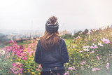 Young woman traveler walking in the flower field