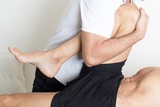 Massage therapist giving a leg massage - 188913948