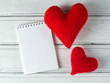two red hearts and a Notepad with copy space. the concept greeting cards
