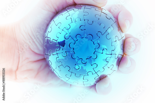 business concept with a hand building puzzle globe on white