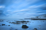Stunning long exposure landscape image of low tide beach with rocks at sunrise - 188946380