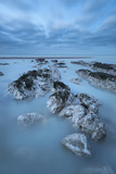Stunning long exposure landscape image of low tide beach with rocks at sunrise - 188946713