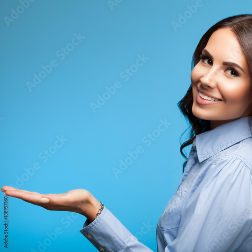Happy smiling showing businesswoman, on blue background