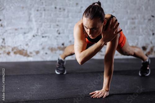młoda piękna kobieta w sportowej robi jedną ręką deski podczas trainnig na krzyż siłownia
