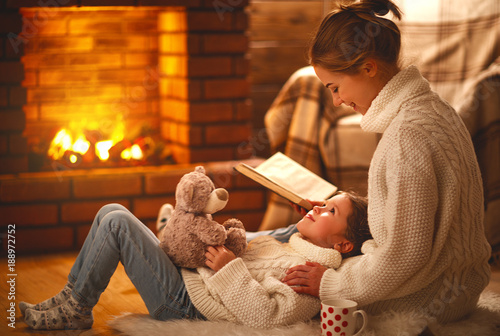 Leinwandbild Motiv family mother and child reading book on winter evening by fireplace.