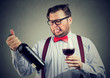Man tasting wine and looking at bottle