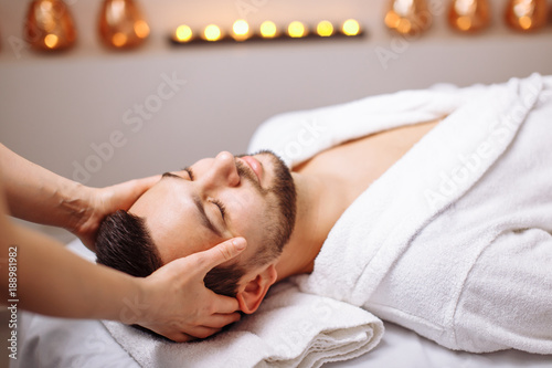 Tuinposter Spa Handsome man during spa head massaging session