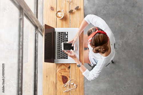 Top view of young woman creates website on laptop computer, reads news or watches video on mobile phone, sits at wooden table near window in her cabinet, drinks hot beverage, uses modern gadgets