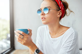 People and recreation concept. Fashionable trendy looking female in shades, drinks hot beverage, enjoys weekends at home, feels relaxed, admires something from window, being alone, calm atmosphere - 189004530