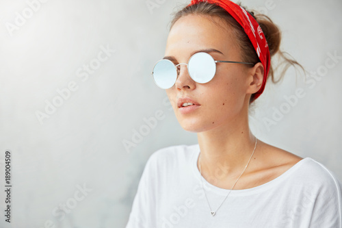 Youth and style concept. Indoor shot of attractive stylish female in round hipster shades stands aginst white background with copy space for your advertisment. Thoughtful fashionable youngster poses