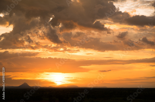 Sunset / sunrise with vivid magenta sky, clouds and mountains dark silhouettes