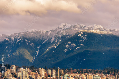 Fotobehang Bleke violet a view from above on the modern city at the foot of the mountains with trees and snow