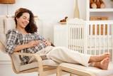 Pregnant woman resting in armchair in nursery - 189012300