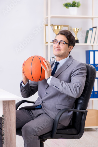Young businessman playing basketball in office during break