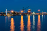 Wharf with crane and lighthouse at dusk