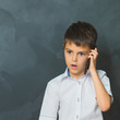 Surprise boy in white shirt talking into the phone, little boss. Communication theme.