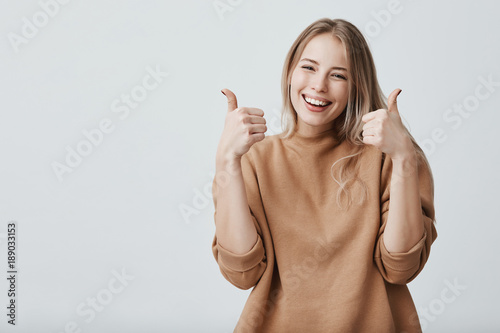 Leinwandbild Motiv Portrait of fair-haired beautiful female student or customer with broad smile, looking at the camera with happy expression, showing thumbs-up with both hands, achieving study goals. Body language