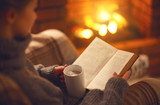 book and cup of coffee in hands of girl on  winter evening near fireplace - 189034343