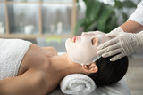 Side view profile of tranquil young woman lying on table at wellness center. Beautician is applying moisturizing mask on her face