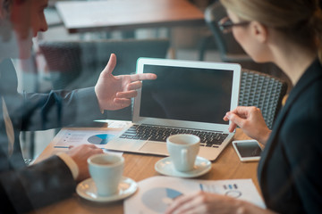 Close up man hand pointing at screen of laptop. Woman looking at it. Work concept