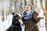Frau geht Gassi mit ihrem Berner Sennenhund im Winter im Schnee - 189049928