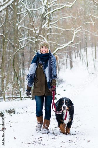 Frau mit ihrem Hund wandert oder geht spazieren im Winter auf einem Weg, der mit Poster