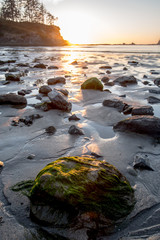 Sun set glows over rocks at low tide