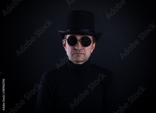studio portrait of a man in sunglasses on a black background