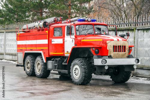 Wóz strażacki w pełnym wyposażeniu rzuca się na wyzwanie wzdłuż asfaltowej drogi obok betonowego ogrodzenia.