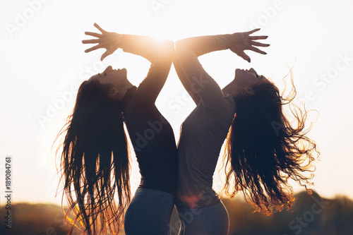 Obraz na płótnie Two young beautiful women doing yoga asana in sun light