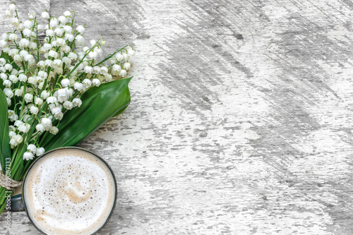 Fotobehang Lelietjes van dalen cup of cappuccino with spring lily of the valley flowers over white wooden table