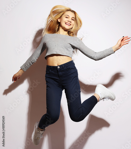 lifestyle and people concept: smiling young woman jumping in air