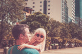 Photo toned in retro style. Little cute blond girl in sunglasses with dad in hands, looking into the lens - 189131507