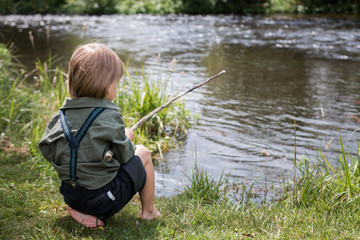 Little boy with old-fashioned fishing rod on a river shore