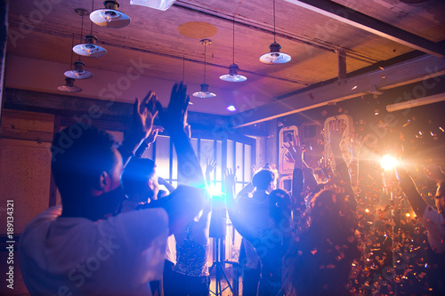 Crowd of cheering young people dancing energetically in night club, lit by stage light under golden glittering confetti blasts, copy space