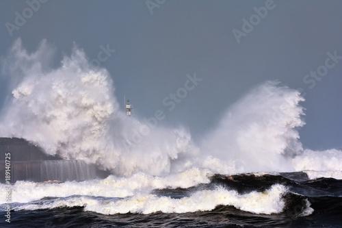 Stormy wave over lighthouse of San Esteban de Pravia. Poster