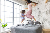 Family fun. Mother and daughter jumping on the bed - 189146526