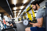 Determined male working out in gym - 189152774