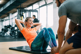 Fototapety Personal trainer assisting woman lose weight