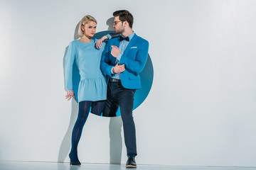 beautiful stylish young couple in blue clothes posing together in hole on grey