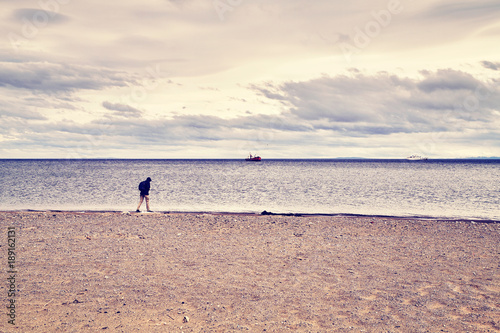 Lonely person walks along a beach, color toned conceptual picture.