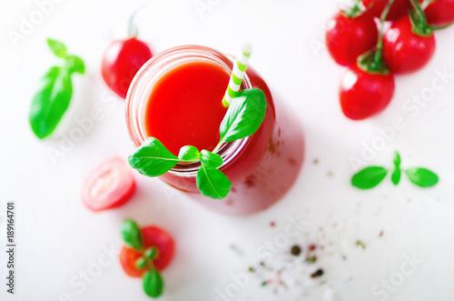 organischer-frischer-tomatensaft-in-einem-glasgefas-in-einem-basilikum-in-einer-kirsche-in-einem-salz-in-einem-pfeffer-und-in-einem-stroh-auf-hellem-hintergrund-sauberes-essen-und-diatkonzept-kopieren-sie-platz