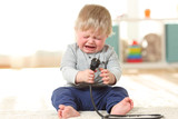 Baby crying holding an an electric plug - 189165131