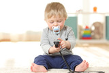 Baby in danger playing with an electric plug - 189165149