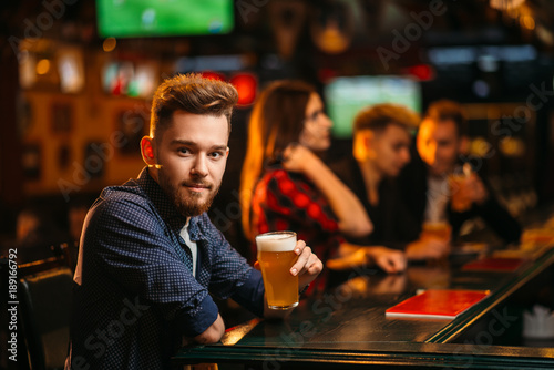 Man holds glass of beer at the bar counter