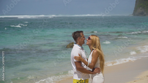 Beautiful couple embracing each other stands on the beach and looks at the sea.Relationships, Beach, couple on romantic travel honeymoon vacation summer holidays romance. Young happy lovers. Travel