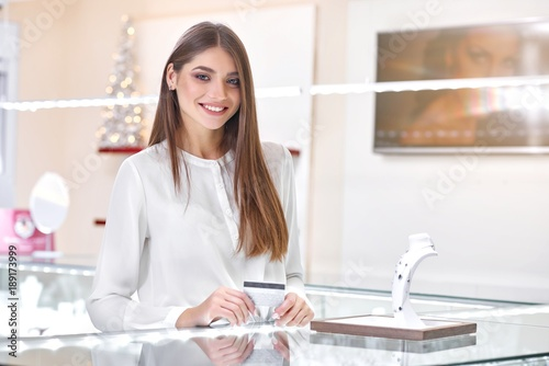 A beautiful brunette woman wearing chic white blouse is standing near the counter of a fashionable jewelry store ready to pay for the necklace designed with blue stones. © serhiibobyk