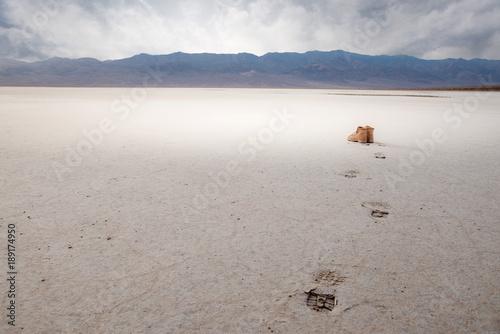 Foto op Canvas Donkergrijs traces de pas et chaussures dans le désert