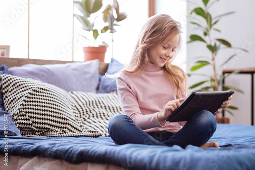 Leisure. Attractive content fair-haired girl smiling and using her tablet while sitting on the bed