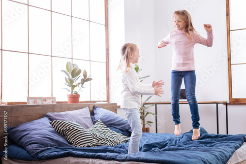 Amusement. Funny joyful fair-haired sisters smiling and jumping on the bed while having fun together